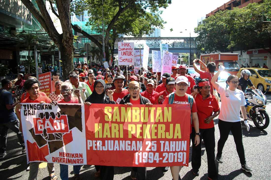"""Demonstranter i Kuala Lumpur, Malaysia håller upp en banderoll med orden """"höj lönen och stoppa diskrimineringen""""."""