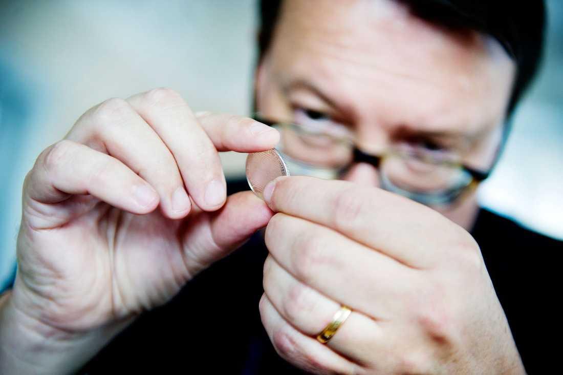 Ian Wiséhn, museidirektör på Myntkabinettet studerar de förfalskade enkronorna, på ena sidan med texten 'Vår horkarl till kung'.