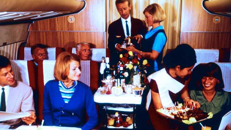 Passagerarna bjuds på drinkar på flight till Asien, 1960-tal.