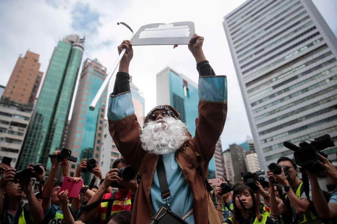 En demonstrant utklädd till Moses håller upp en stentavla vid en protest i Hongkong.
