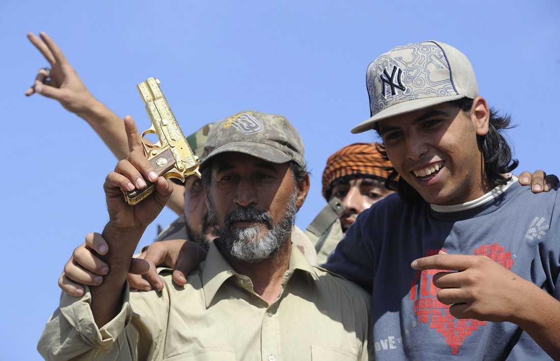 NTC-soldater håller upp en gyllene pistol som enligt uppgifter tillhört Gaddafi.