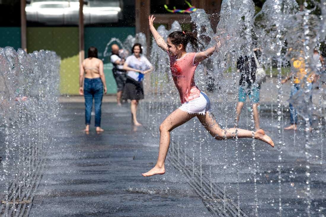 Ett barn svalkar sig i en fontän i Rysslands huvudstad Moskva den 11 juni, när temperaturen låg kring 30 grader.