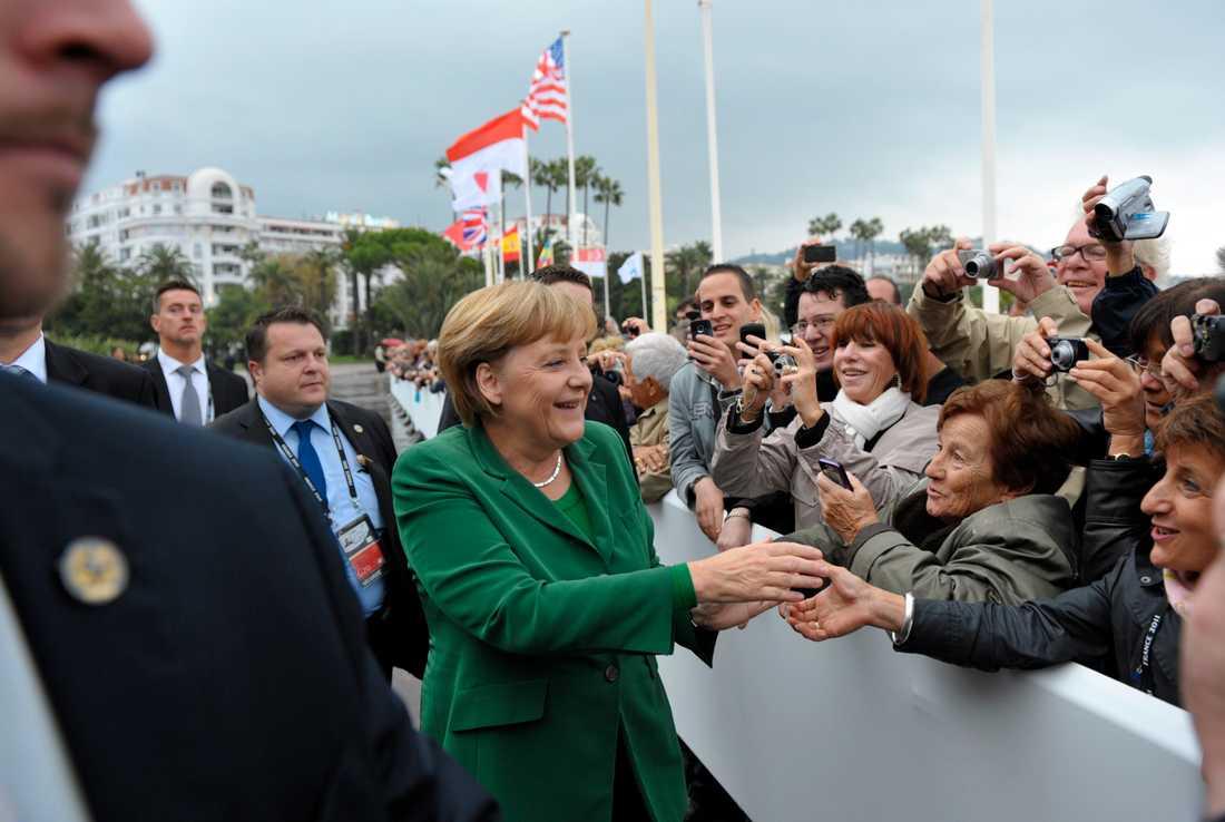 Tysklands Angela Merkel hälsar på folket när hon anländer till G20.