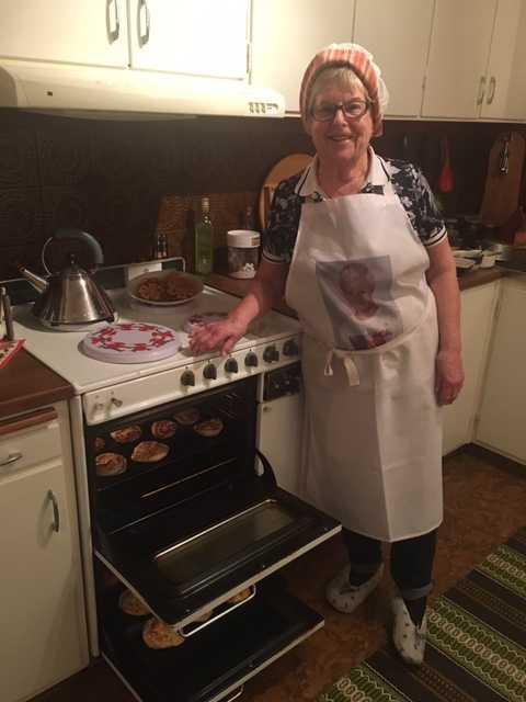 Glad Inger Andreasson tillammans med sin 55 år gamla spis och nybakade bullar.