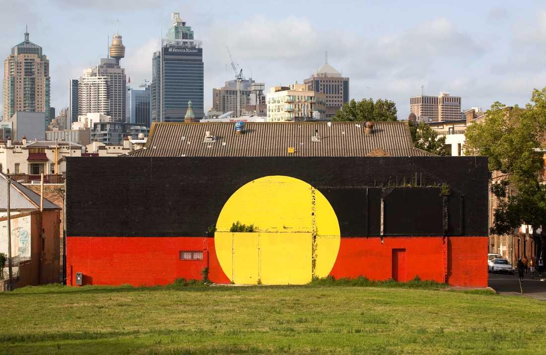 Australiens ursprungsbefolkning aboriginernas flagga målad på en vägg i Sydney. Arkivbild.