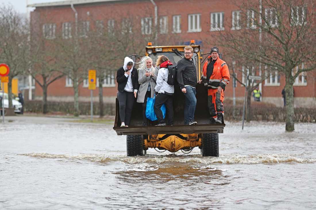 Personer får hjälp av en hjullastare att ta sig genom vattenmassorna.