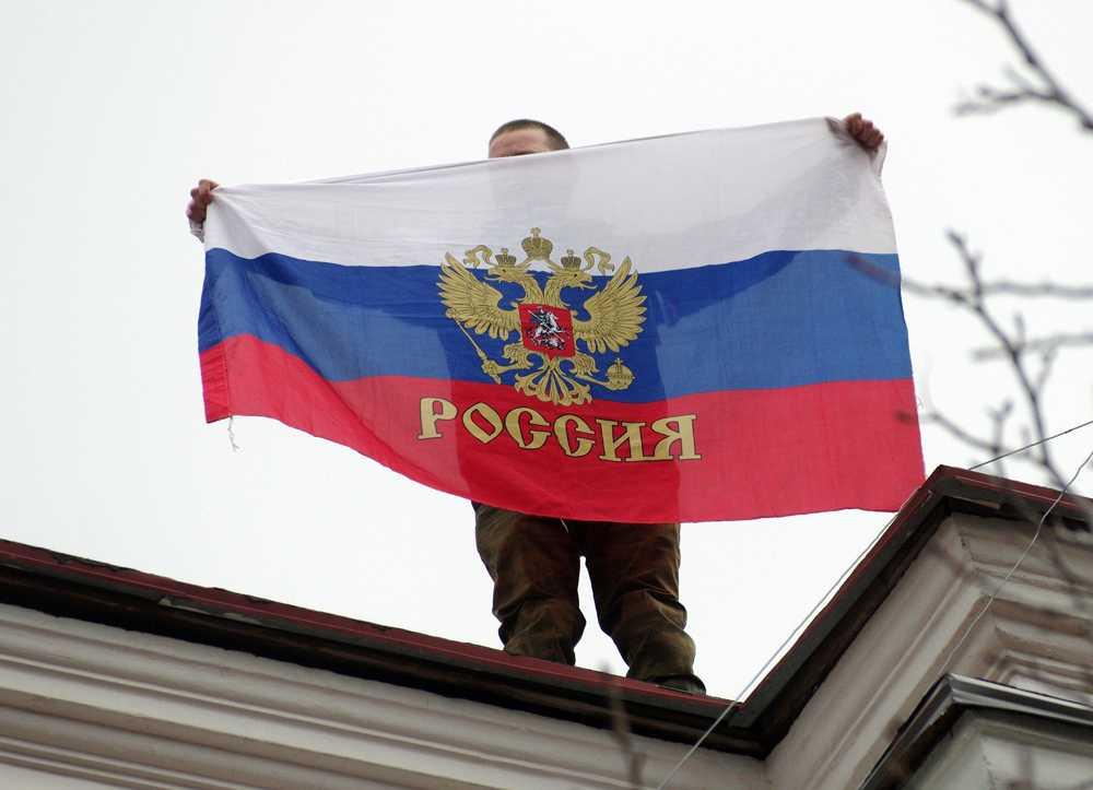 En man håller upp en rysk flagga på ett tak, någonstans på Krimhalvön. Spänningarna har de senaste dagarna ökat rejält.