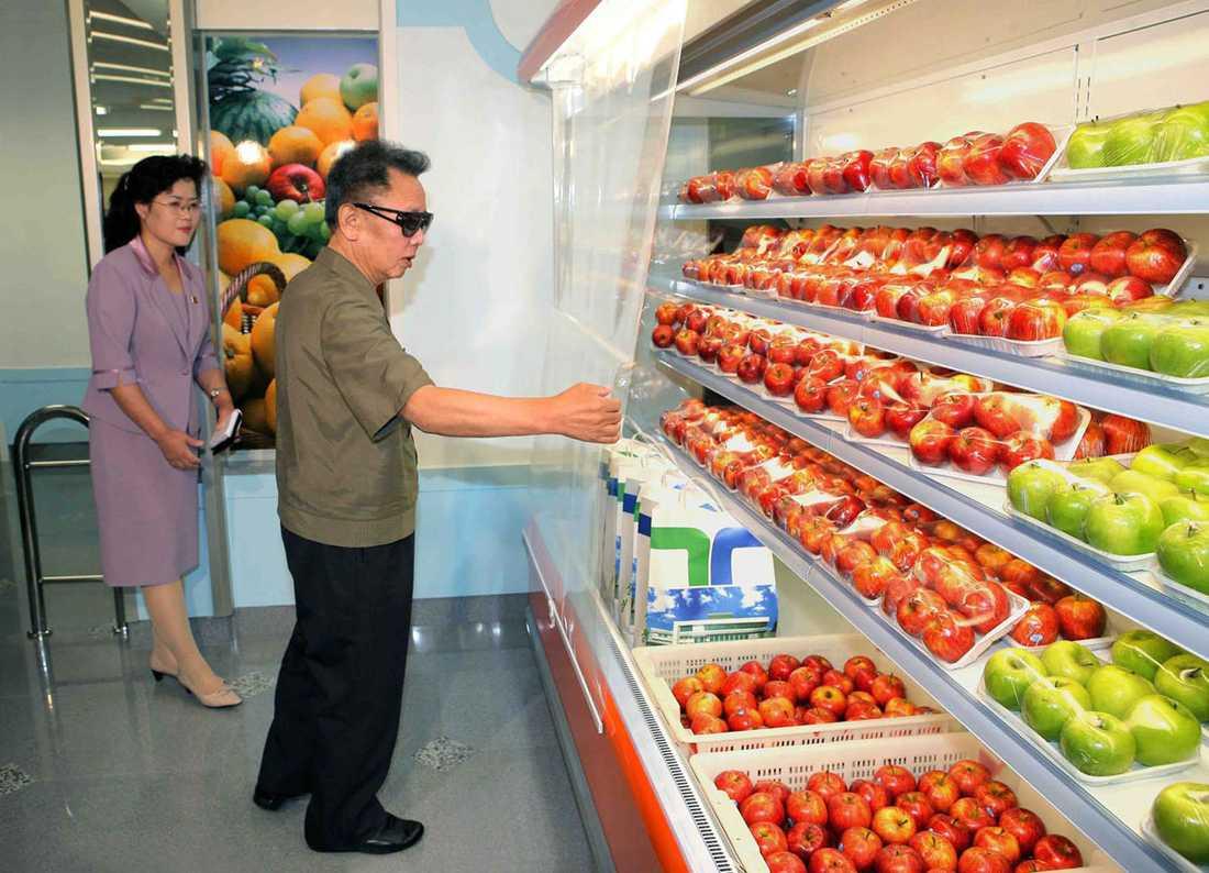 KIM TITTAR PÅ ÄPPLEN I Demokratiska folkrepubliken Korea finns det både gröna och röda äpplen. Som synes dignar butikshyllorna av det stora utbudet.