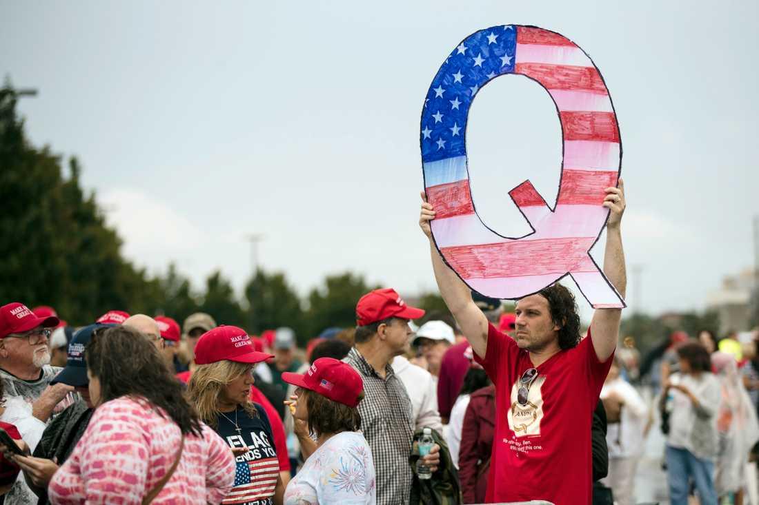 En man håller upp ett stort Q målat som en amerikansk flagga under ett av president Donald Trumps kampanjmöten i delstaten Pennsylvania i början av augusti.