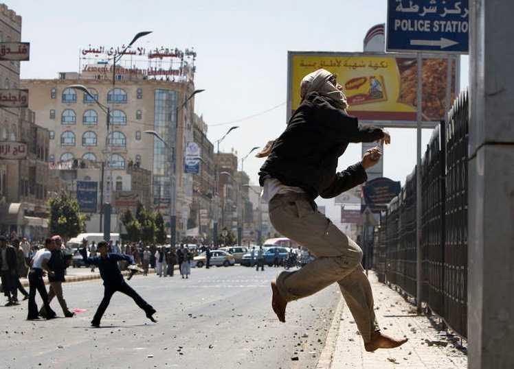 Demonstranter kastar sen mot en polisstation i Jemen.