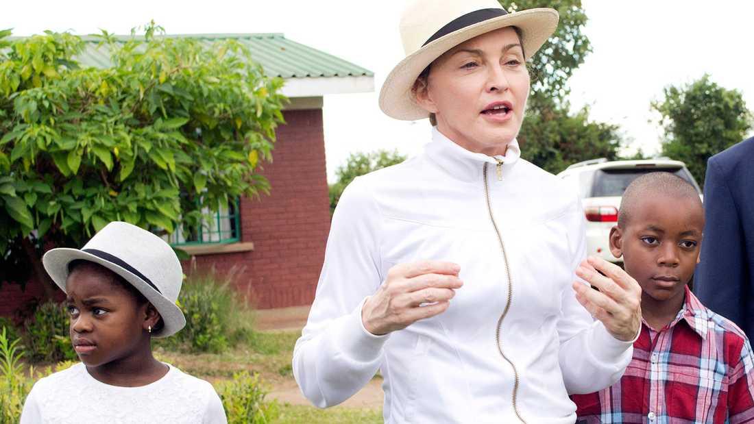 Madonna på besök i Malawi 2013 med sina adopterade barn Mercy (till vänster) och David.