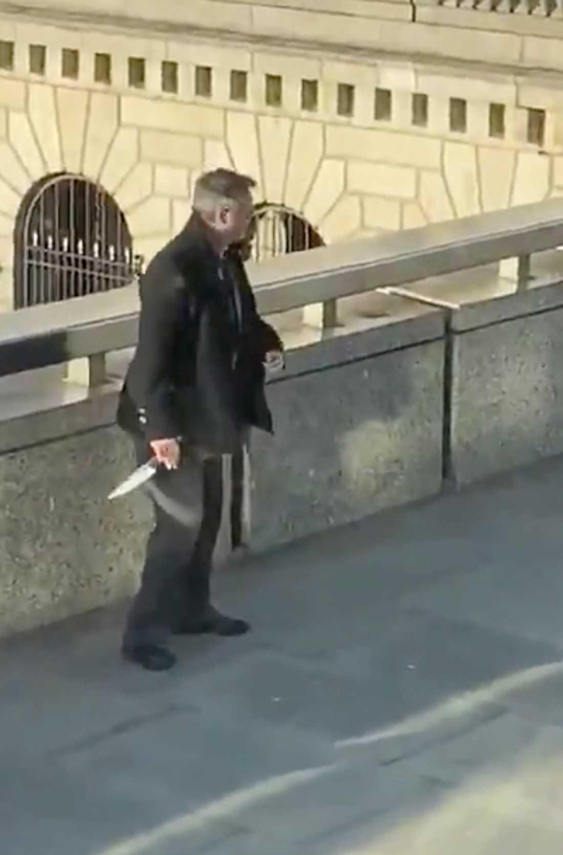 En stillbild från en video visar en åskådare som håller en kniv.