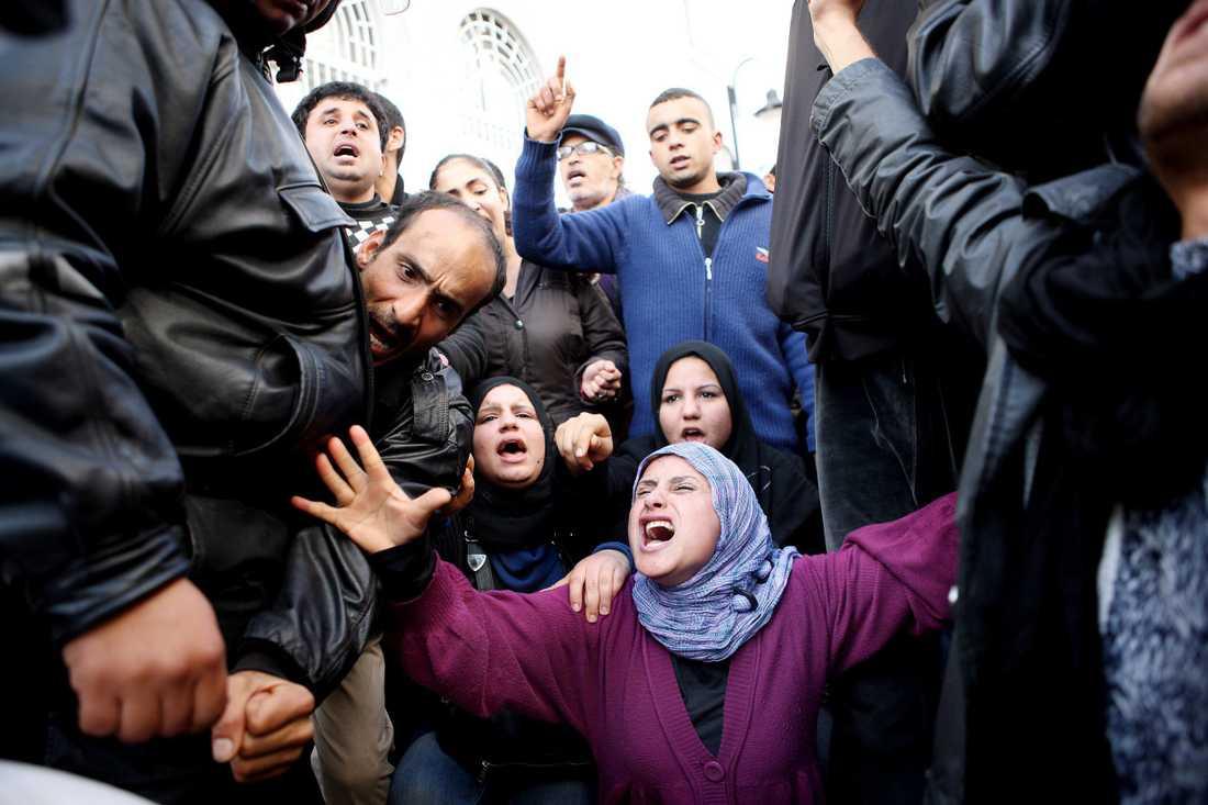 Knäfallande framför de beväpnande poliserna sträcker Monia Amsuri armarna mot himlen och ropar; Leve ett fritt Tunisien.