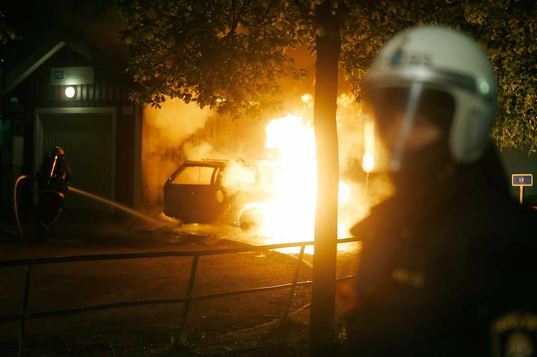 Brandman släcker en brinnande bil i Rinkeby.