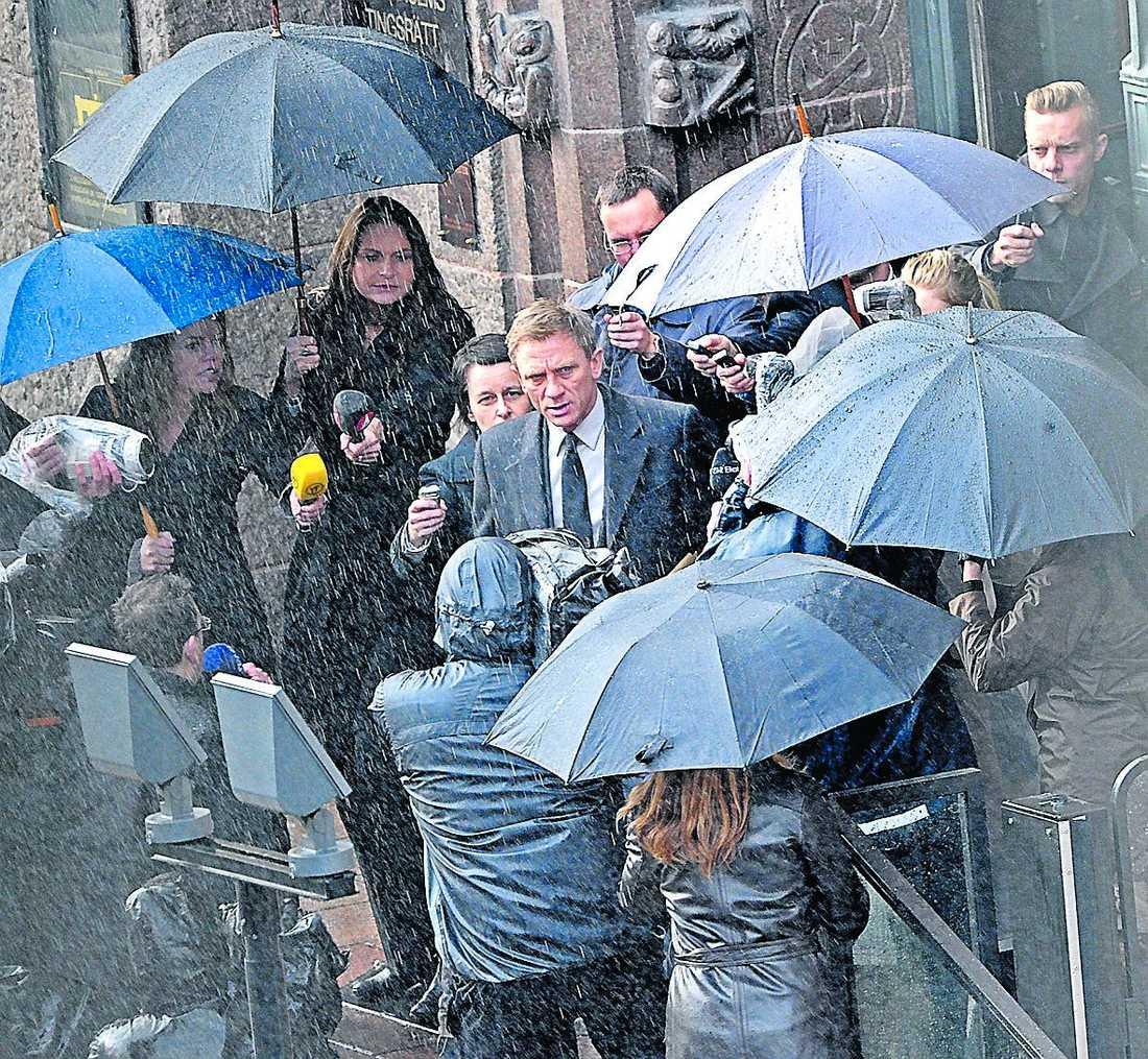 """En stor regnrigg blöter ner Daniel Craig under inspelningen av """"Dragon tattoos"""" utanför Stockholms tingsrätt i går."""