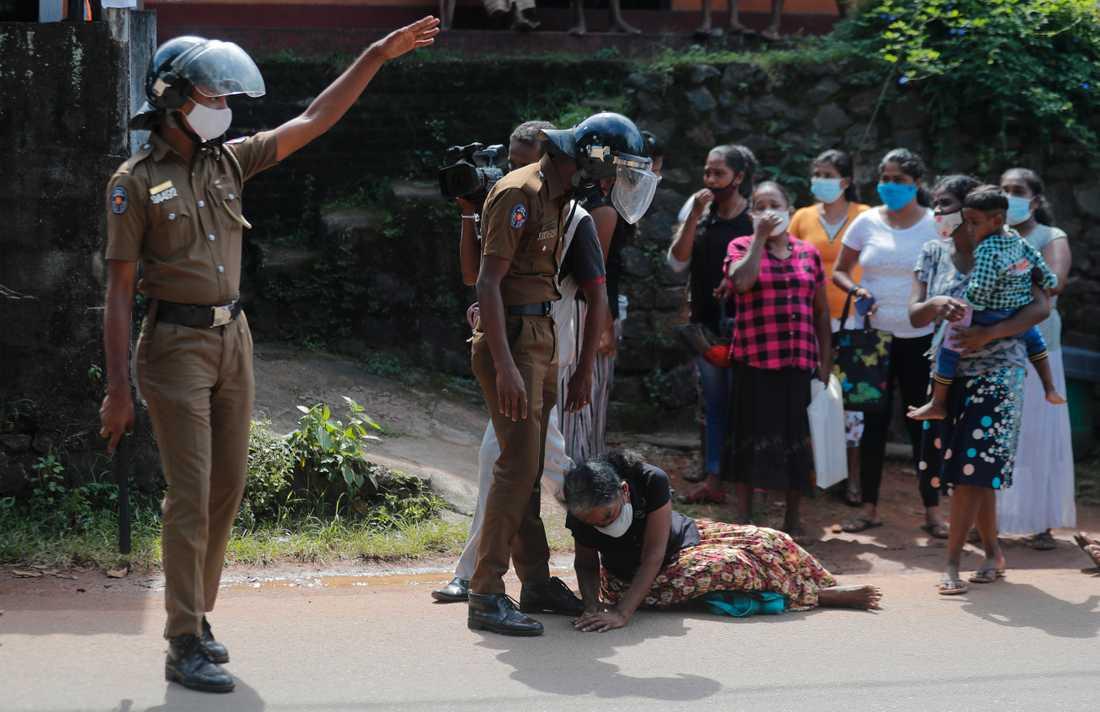 En kvinna vädjar till polisen utanför Mahara-fängelset om att få information om sin fängslade familjemedlem.