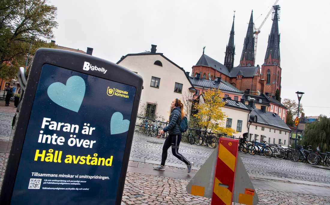 En affisch från Uppsala kommun som uppmanar att hålla avstånd och att faran inte är över när det gäller smittspridningen.