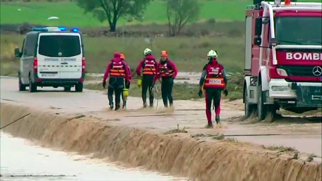 Personal från räddningstjänsten nära platsen där två personer omkom i en vattenfylld bil sydost om staden Valencia.
