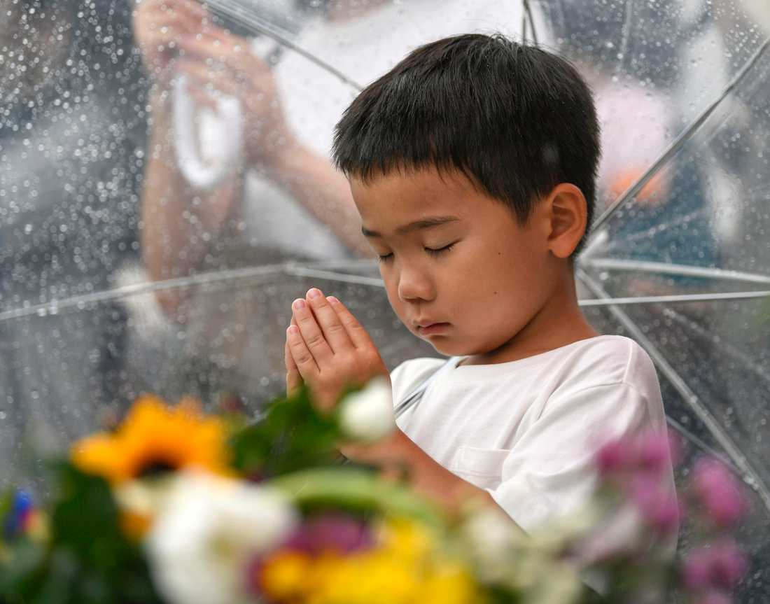 En liten pojke deltar i minnesceremonin.