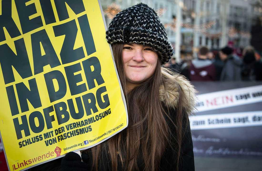 Ung kvinna håller upp ett plakat under demonstrationen mot Norbert Hofer.