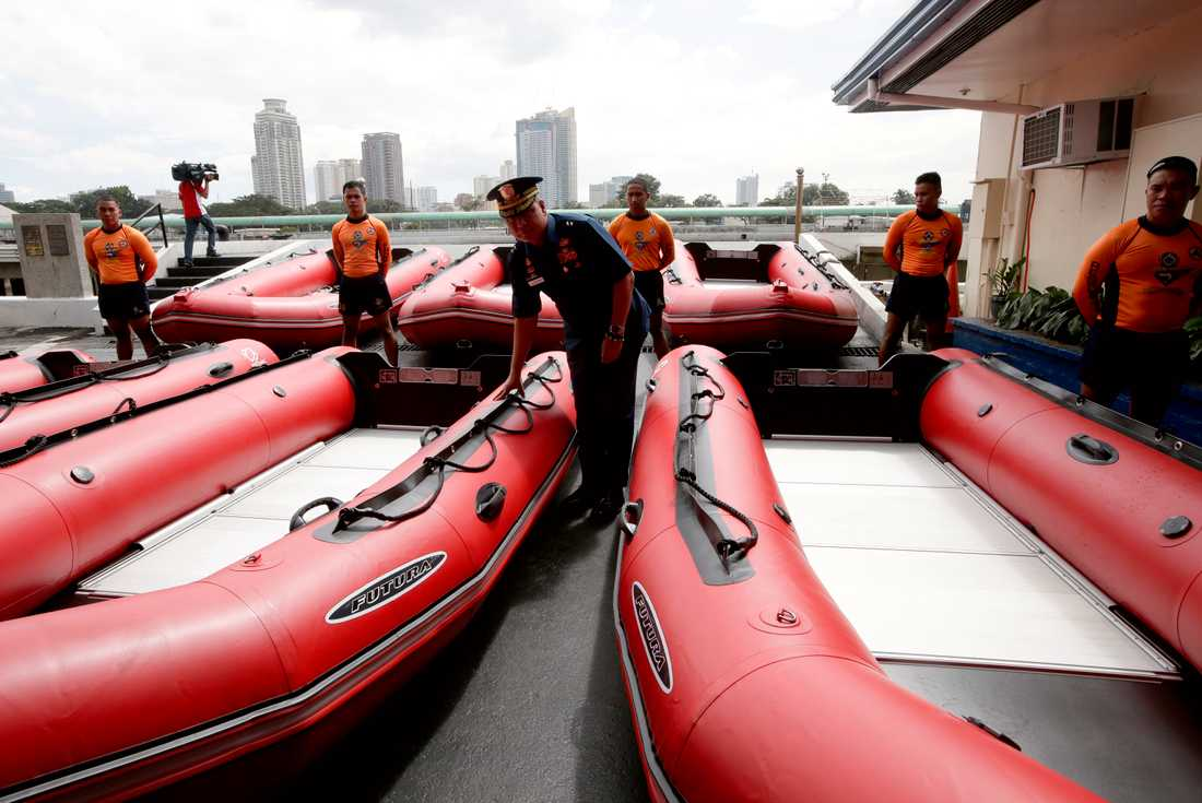 Kustbevakningschefen kontrollerar nya gummibåtar i Manila.