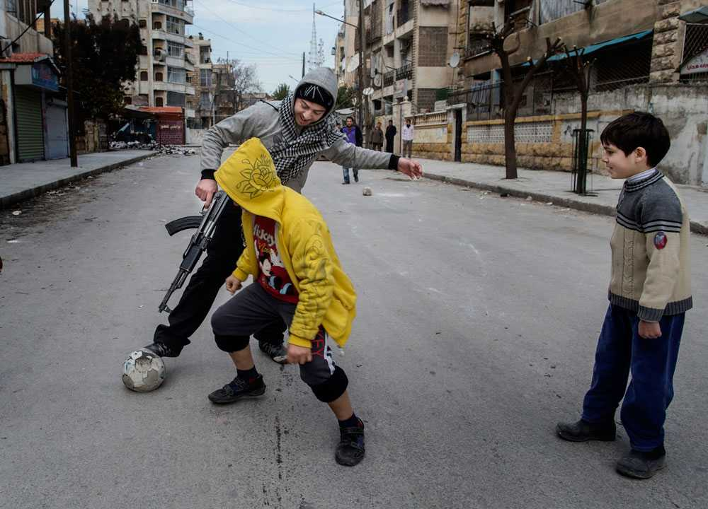 NICLAS HAMMARSTRÖM En soldat från Free Syrian Army spelar fotboll med barnen i stadsdelen Saif al-Dawlah i Aleppo. Runt hörnet på gatan bakom dom rasar strider.