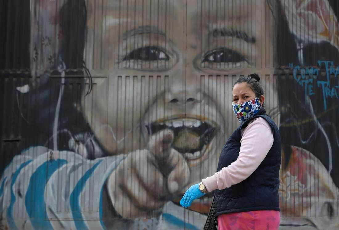 En kvinna i munskydd och handskar tar en promenad i Bogotas utkanter i Colombia. Arkivbild.