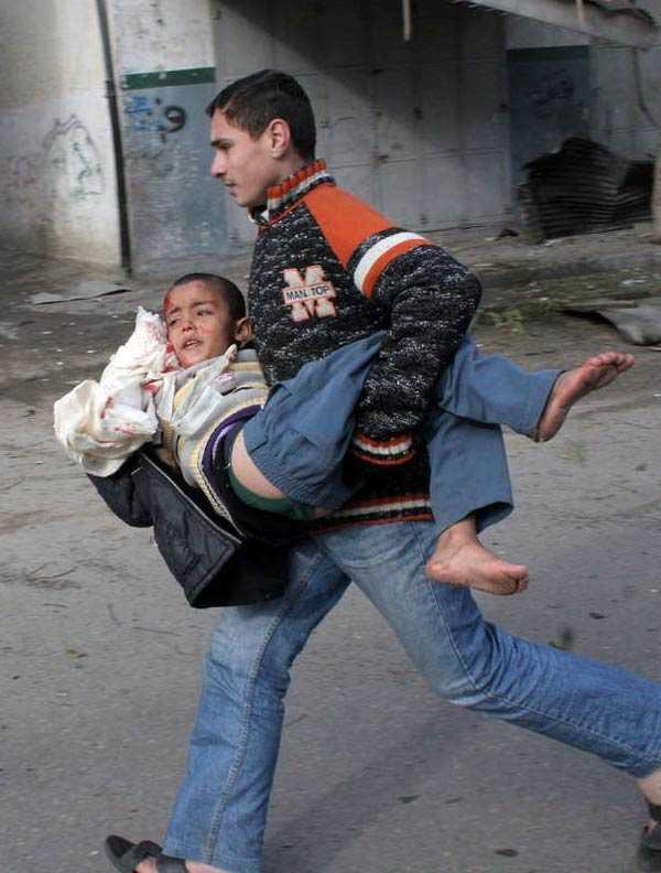 Stridsplanen har flugit bort för den här gången. En palestinsk pojke bär sin chockade och skadade bror.