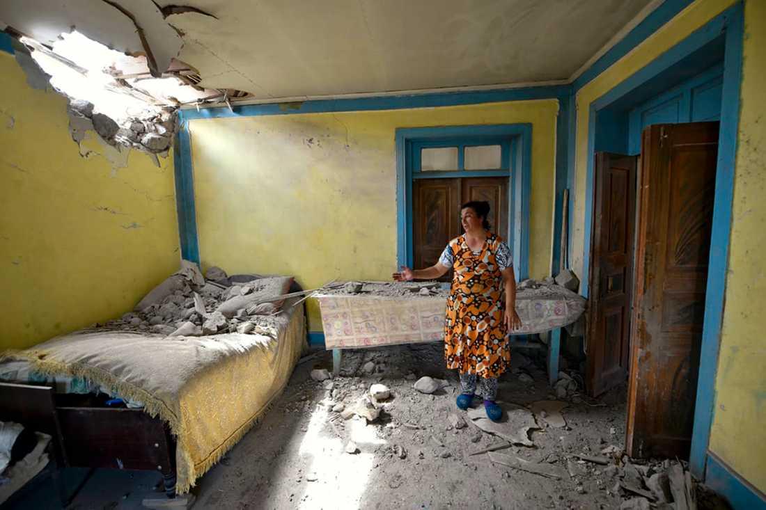 En kvinna i den azeriska Tovuz Rayonu-distriktet visar upp sitt hem som skadats i den senaste tidens stridigheter mellan Armenien och Azerbajdzjan. Arkivbild.