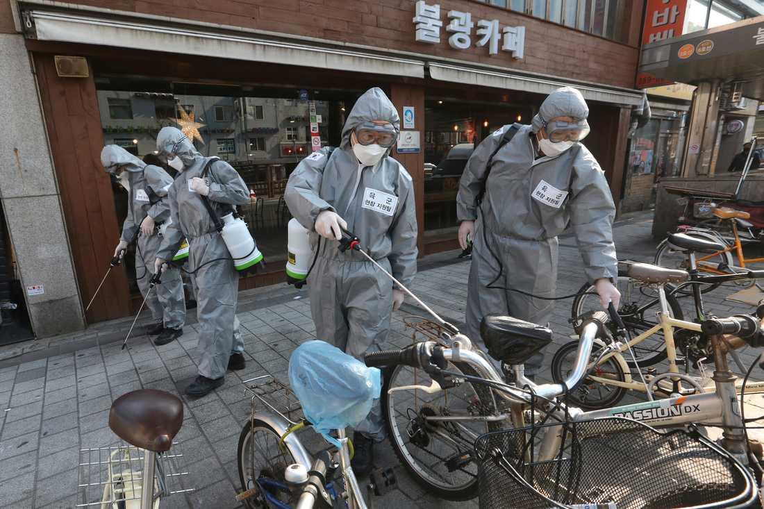Sydkoreanska soldater i skyddsutrustning desinficerar en gata i Seoul. Arkivbild.