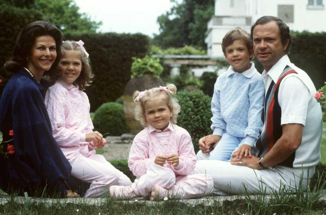 Sommarfamiljen Kungafamiljen samlad på Solliden, Öland. Kronprinsessan Victoria i mamma drottningens knä, prinsessan Madeleine i mitten och prins Carl Philip i pappa kungens knä.