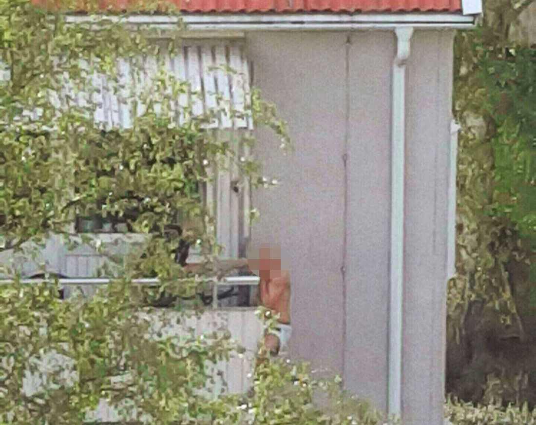 Misstänkte mördaren hänger från balkongen. På balkongen står även en polis, till stora delar skymd av lövverket.
