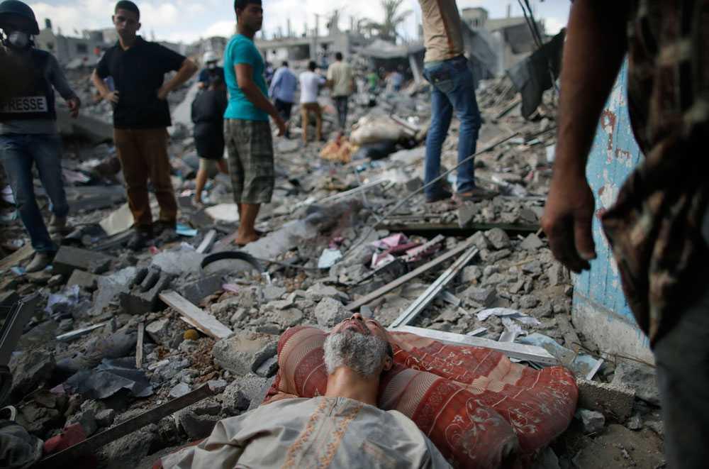 En palestinsk man lägger sig ner mitt i resterna av hans hus.