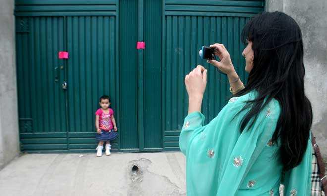 """""""Le mot kameran"""" En kvinna fotograferar sin dotter utanför huset där terrornätverket al-Qaidas ledare Usama bin Laden dödades i måndags."""