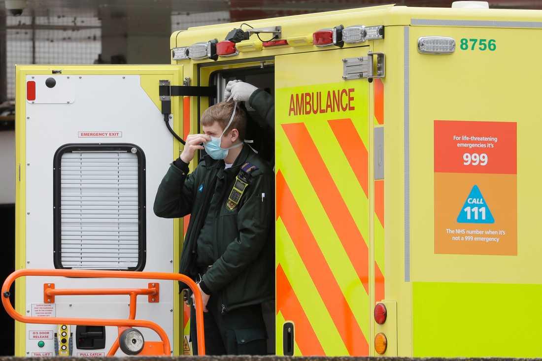 En vårdanställd får hjälp av en kollega att få på sig ett munskydd, vid ett sjukhus i London.