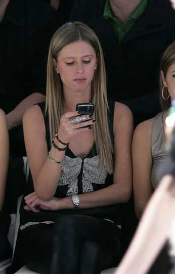 Nicky Hilton är sådär intresserad av visningen eller så sms:ar hon sin syster om de senaste trenderna...