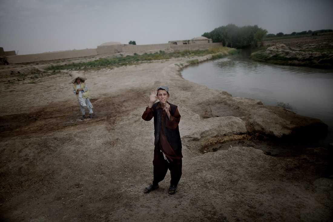 En pojke vinkar när soldaterna passerar genom byn.