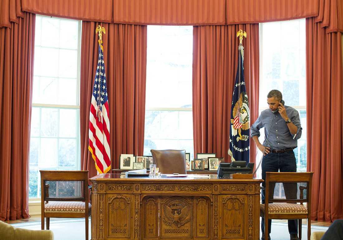 Obama pratar i telefon i Ovala rummet.