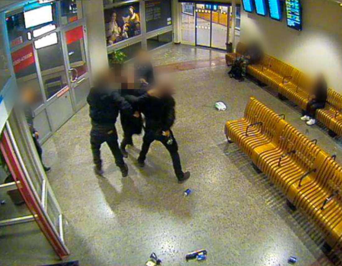 En av de tre männen kastar sig mot polismannen.