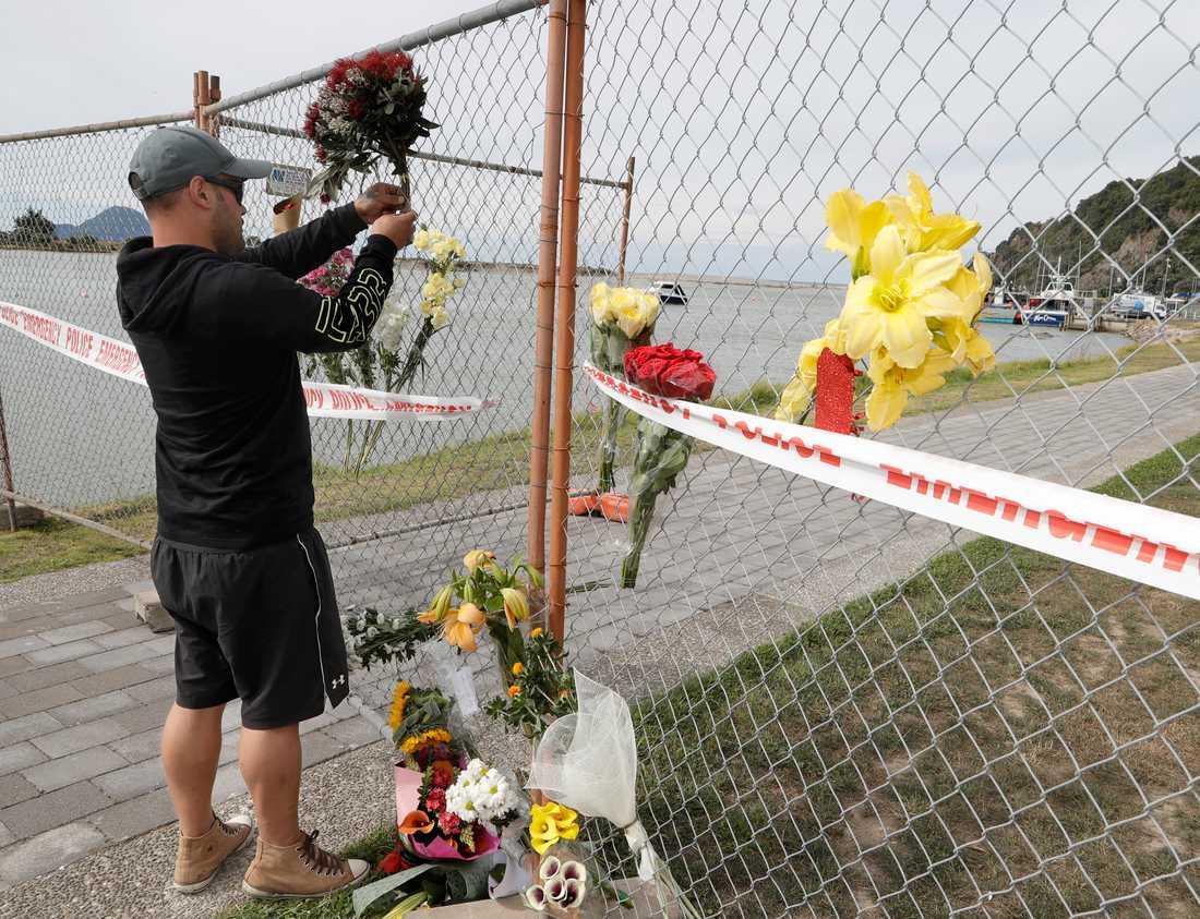 En man lämnar blommor till minne av de omkomna efter vulkanutbrottet på White Island.