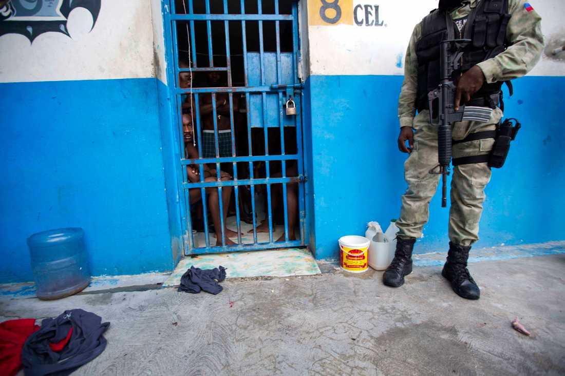 En polisofficer håller vakt utanför en cell i fängelset i kuststaden Arcahaie, Haiti.