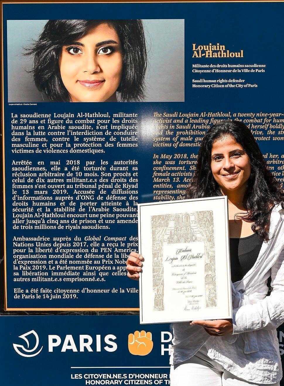Lina al-Hathloul, lillasyster till fängslade Loujain al-Hathloul, framför en bild på sin syster.