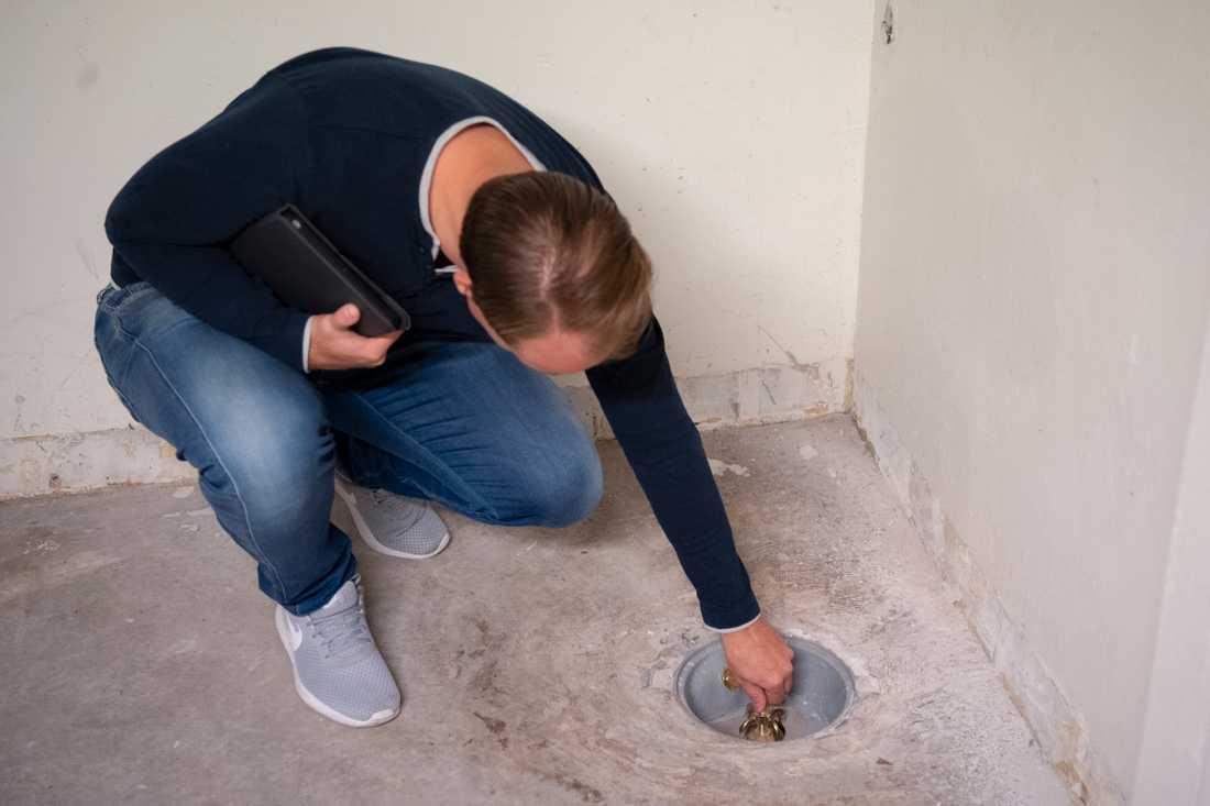 """Richard Malm kontrollerar att """"spindeln"""" som finns monterad i golvbrunnen fungerar."""