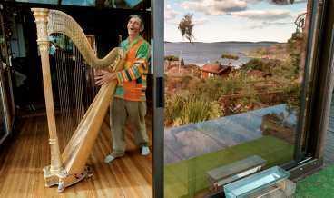byggt i ädelträ Henry Soludde spelar harpa i det jättelika och excentriska huset som är byggt helt av ädelträ.