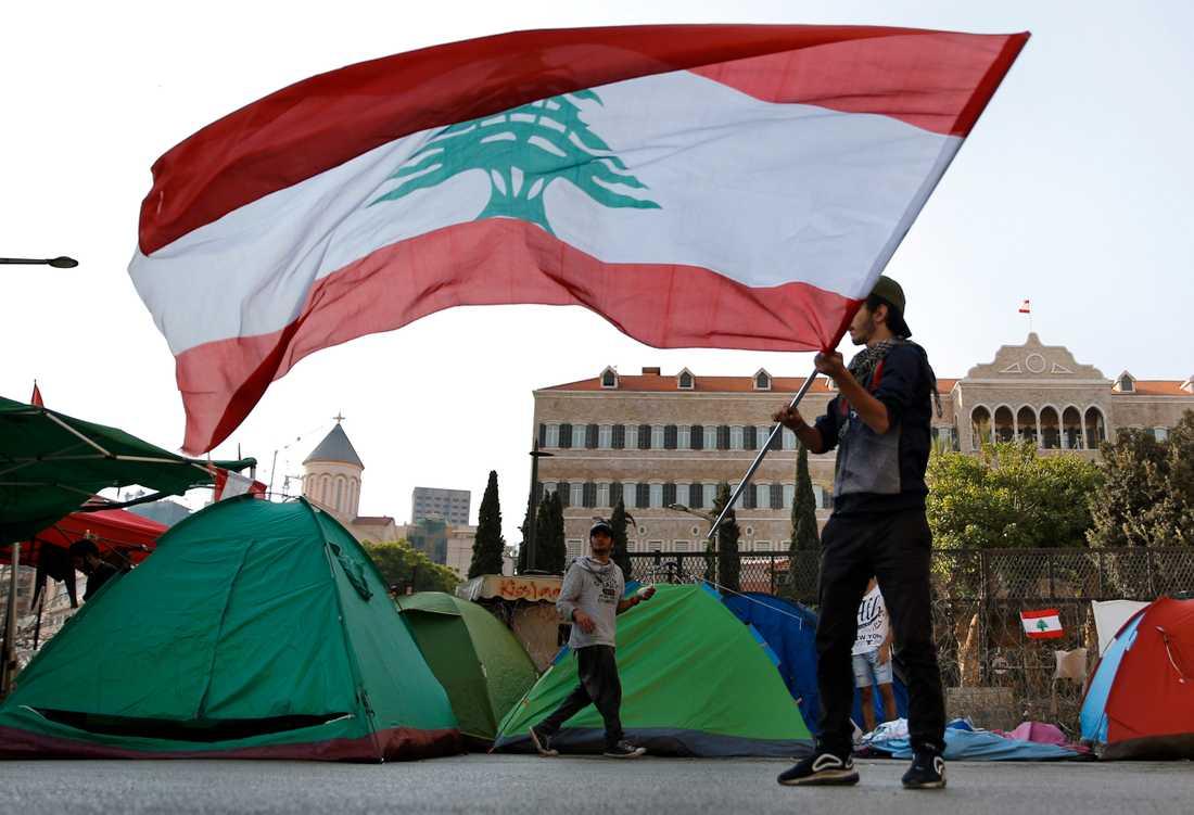 En demonstrant med den libanesiska flaggan under regeringskritiska protester i Libanons huvudstad Beirut den 31 oktober.