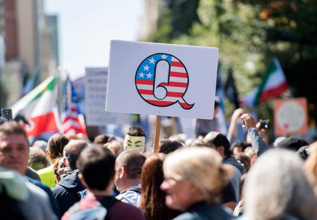 Människor demonstrerar i kanadensiska Montréal. Q-tecknet är en symbol för Qanon, en konspirationsrörelse som tror att Donald Trump är inblandad i ett hemligt krig mot en pedofilstyrd maktelit.