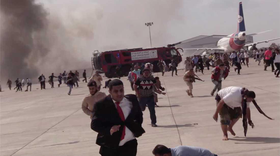 Personer springer efter en explosionen på flygplatsen Aden, Jemen.