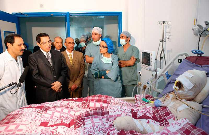 hans död skapade kaos i tunisien Mohamed Bouazizi, 26, sålde frukt och grönsaker för att överleva dagen. Förra månaden konfiskerade myndigheterna hans vagn. I ren desperation hällde han en dunk bensin över sig och tände på. Han fick svåra brännskador och president Zine El Abidine Ben Ali, här klädd i svart, besökte honom på sjukhuset. Bouazizi dog i början av året. Det var signalen som tusentals universitetsstudenter väntat på. Som svar på Bouazizis död tågade de ut i protest mot presidenten som styrt Tunisien med järnhand i drygt 23 år.