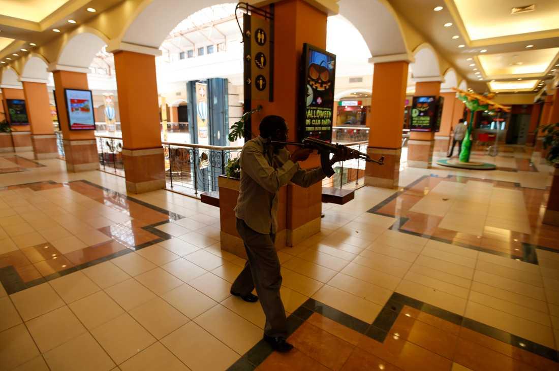 En beväpnad polisman söker igenom gallerian