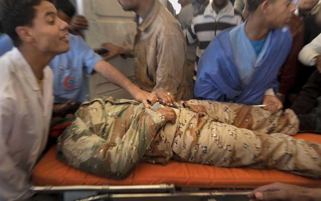 Skadad En läkare håller hårt i en skadad rebell som förs till sjukhuset i Ajdabiya, Libyen. Totalt dödades 30 rebeller igår av Gaddafis styrkor.